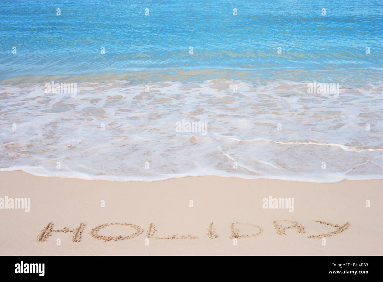 The word 'Holiday' written in the sand on a tropical beach - Stock Image