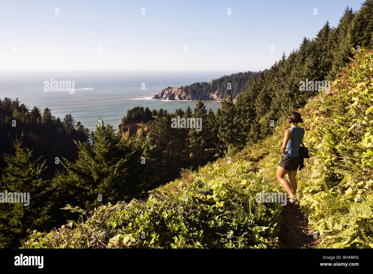 A woman wearing summer clothes hikes Neahkahnie Mountain, a coastal trail in northwest Oregon, and pauses to look - Stock Image