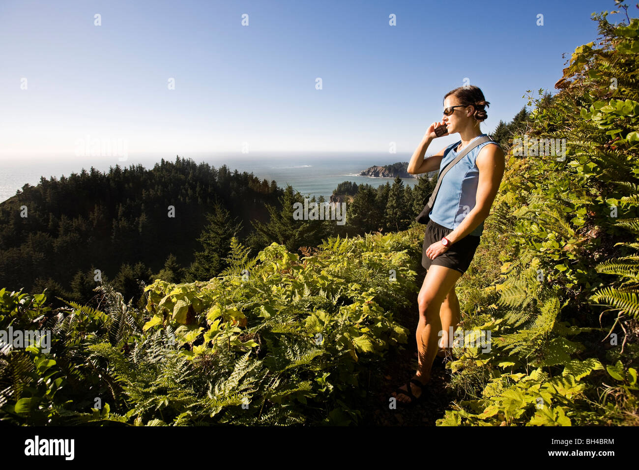 A woman with sunglasses and summer clothes hikes a coastal trail in northwest Oregon, and pauses to answer her cell - Stock Image