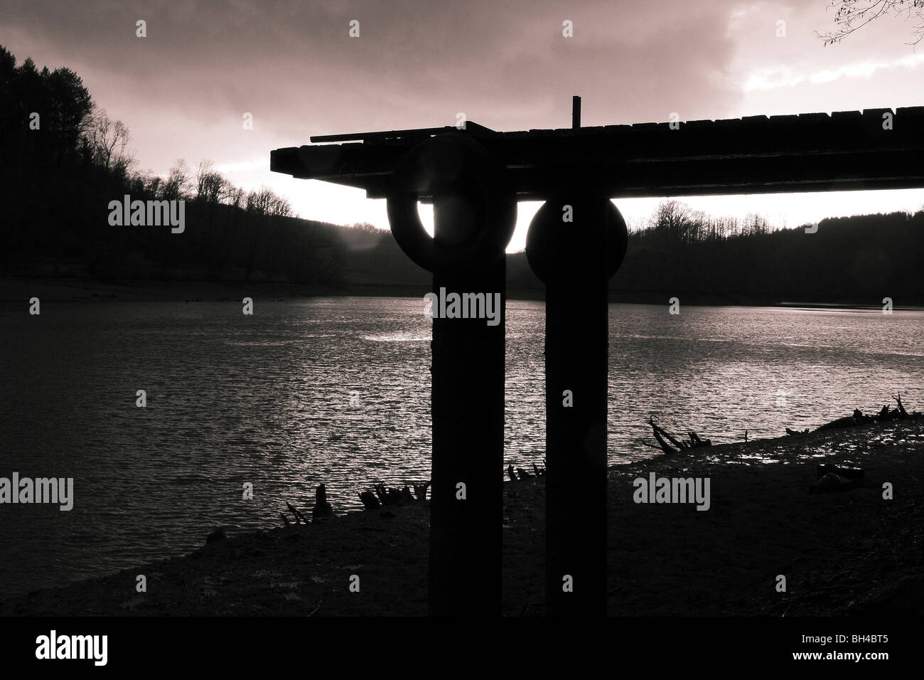 Tinted black and white composition of an old jetty above a drained lake in the Limousin region against stormy sky. - Stock Image