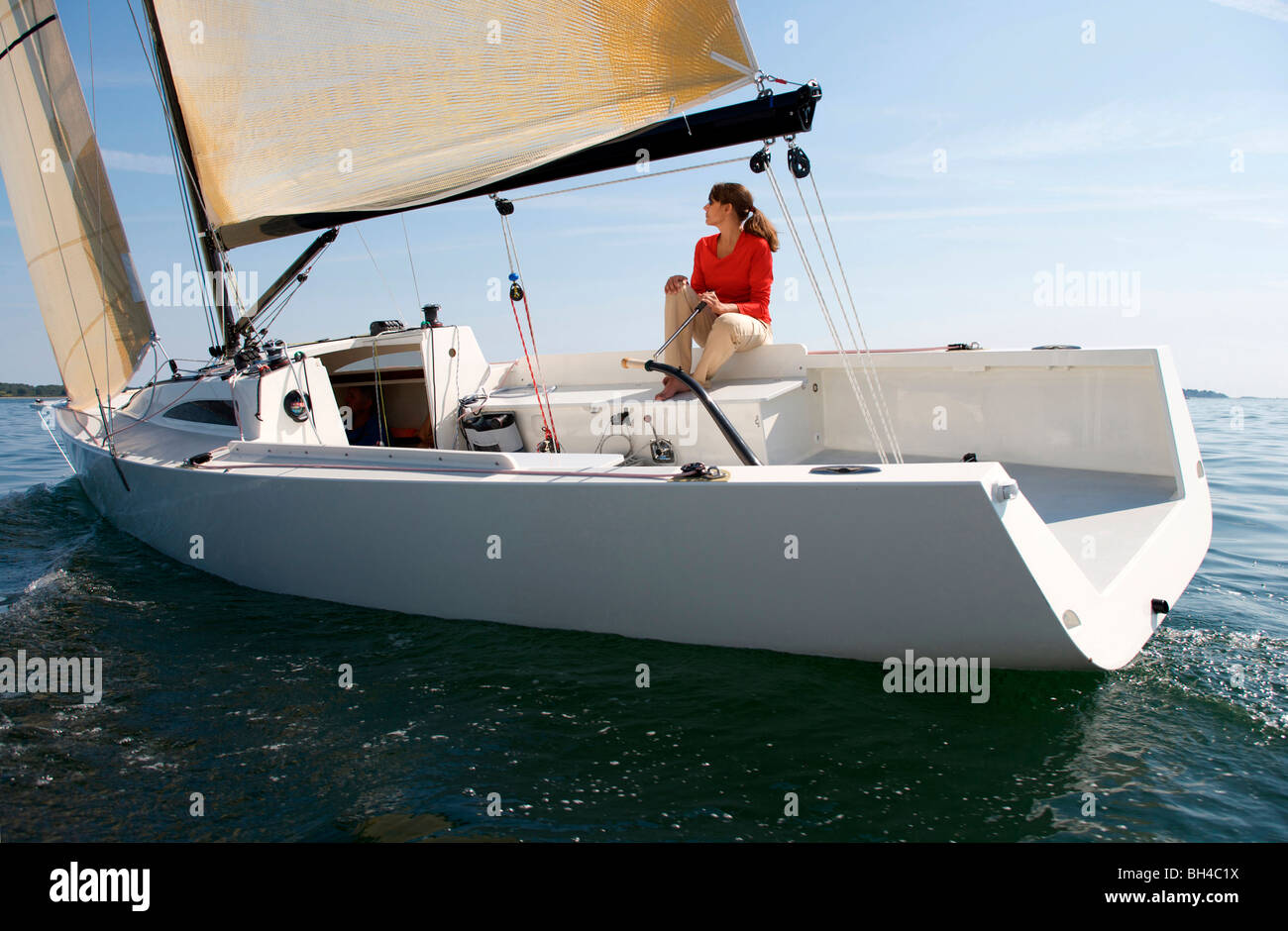 A woman enjoying a sunny day on board a daysailer on Casco Bay, Maine. - Stock Image