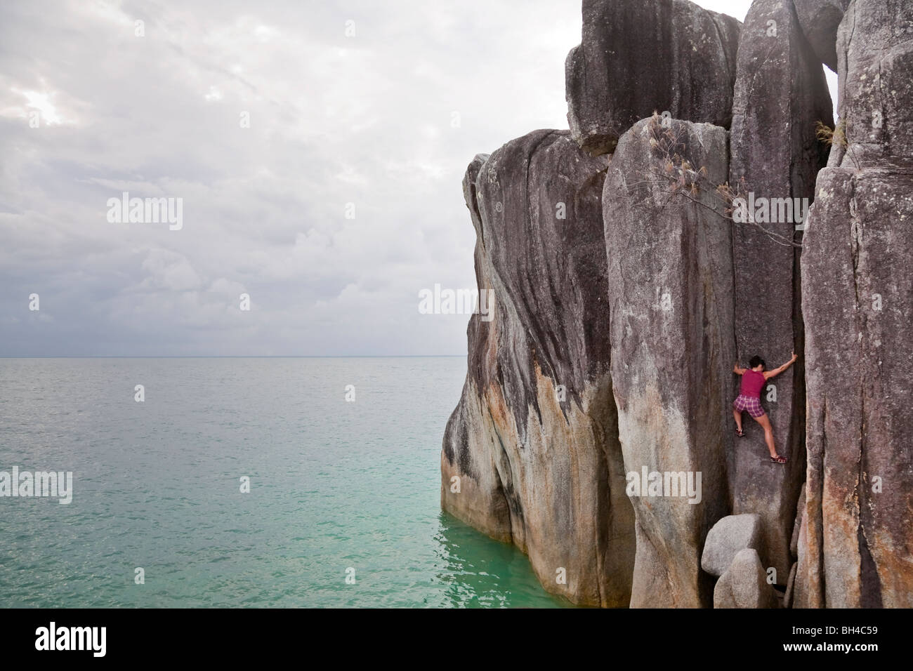 A woman climbs a granite rock pillar over the ocean on Coombe Island, Queensland, Australia. - Stock Image