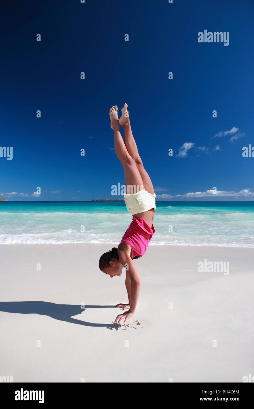 Young woman performing a hand stand on a deserted tropical beach - Stock Image