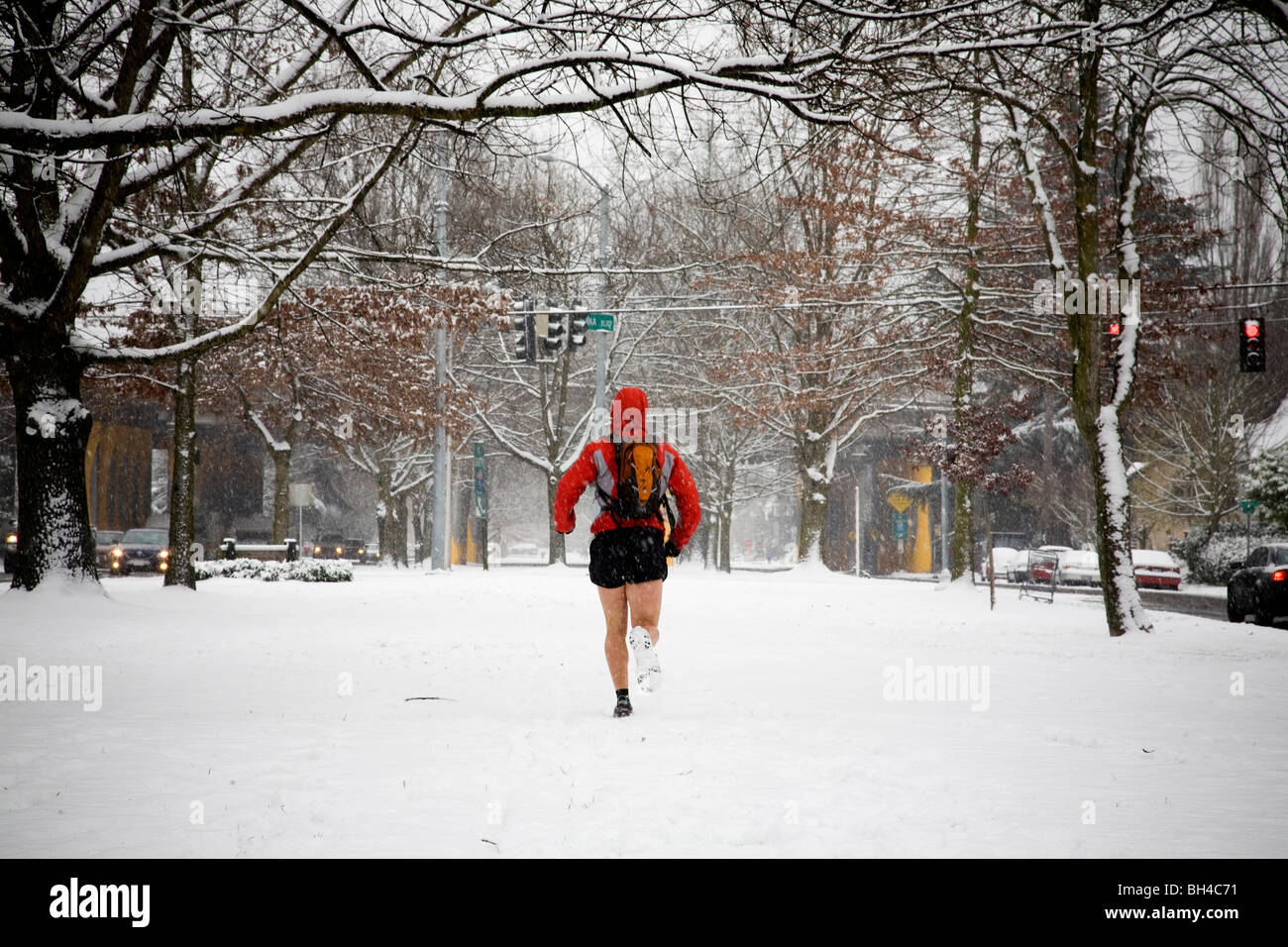 A male runner with a backpack runs down a city street while wearing shorts in the winter. - Stock Image