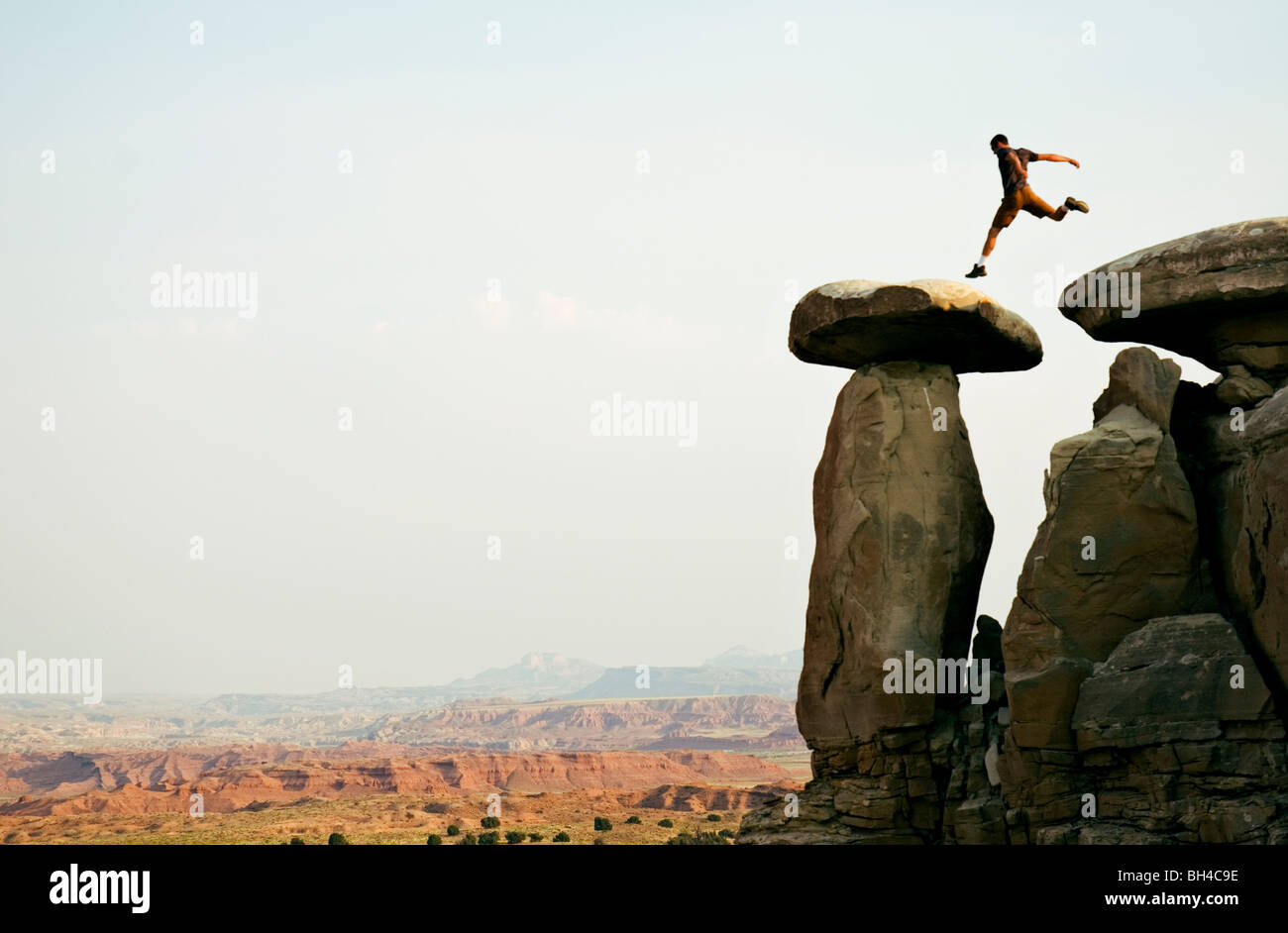 A young man jumps across a set of rocks in Moab, Utah. - Stock Image