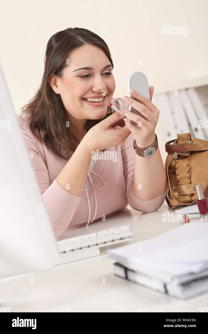 Young businesswoman applying lipstick at office sitting at desk - Stock Image