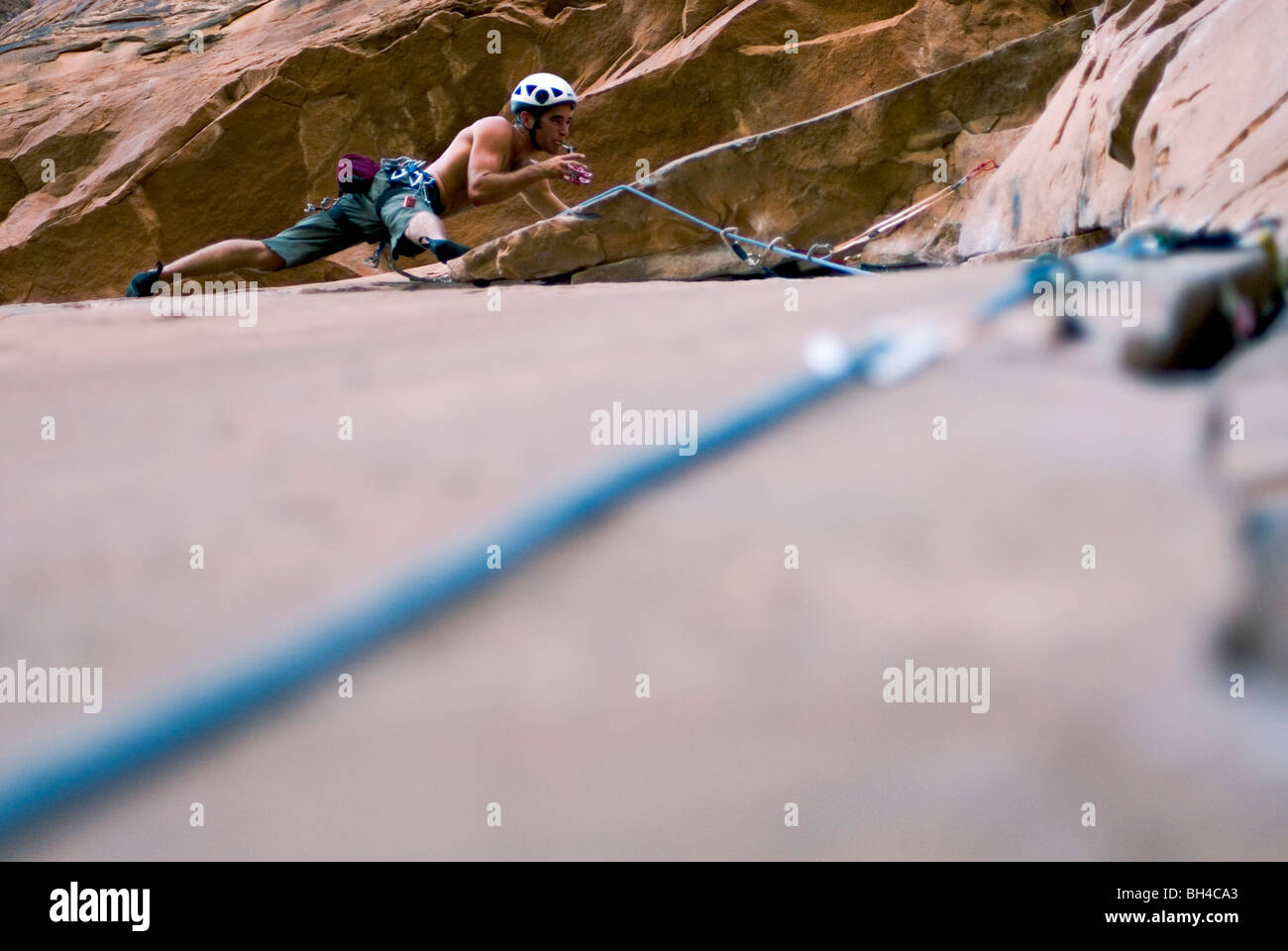 With trad gear in hand, a young man examines the rock climbing route in Moab, Utah. - Stock Image