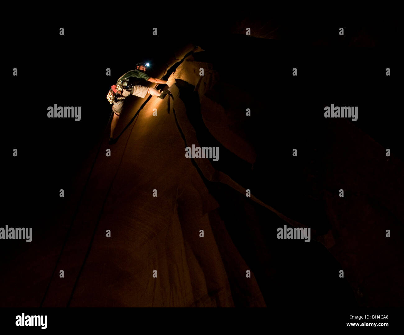 Descending at night, a young man cleans up the trad gear while rock climbing in Moab, Utah. - Stock Image