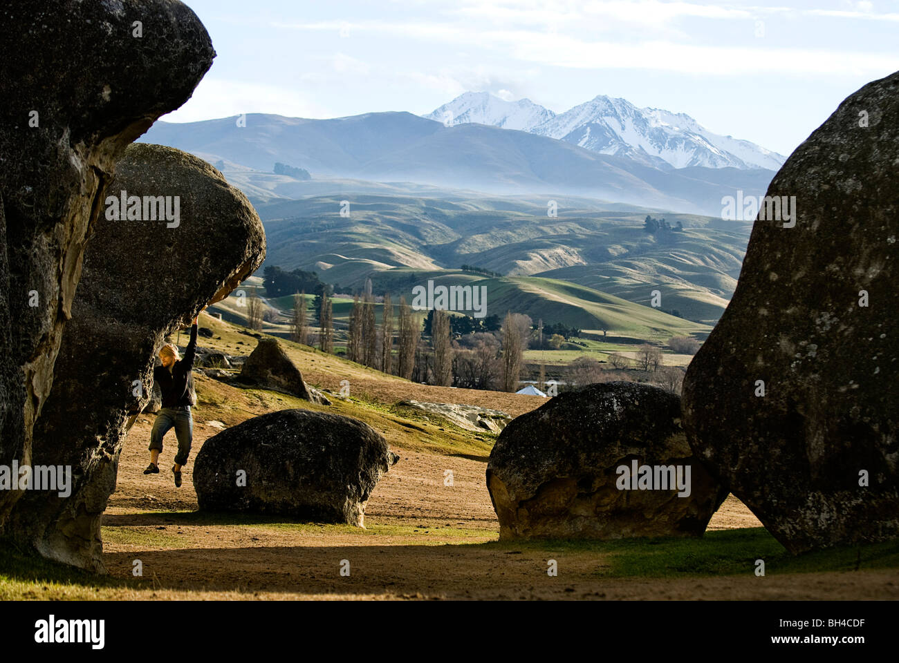 Hanging on with only his hands, a young man searches for a foot hold on a boulder at Elephant Rocks, New Zealand. - Stock Image