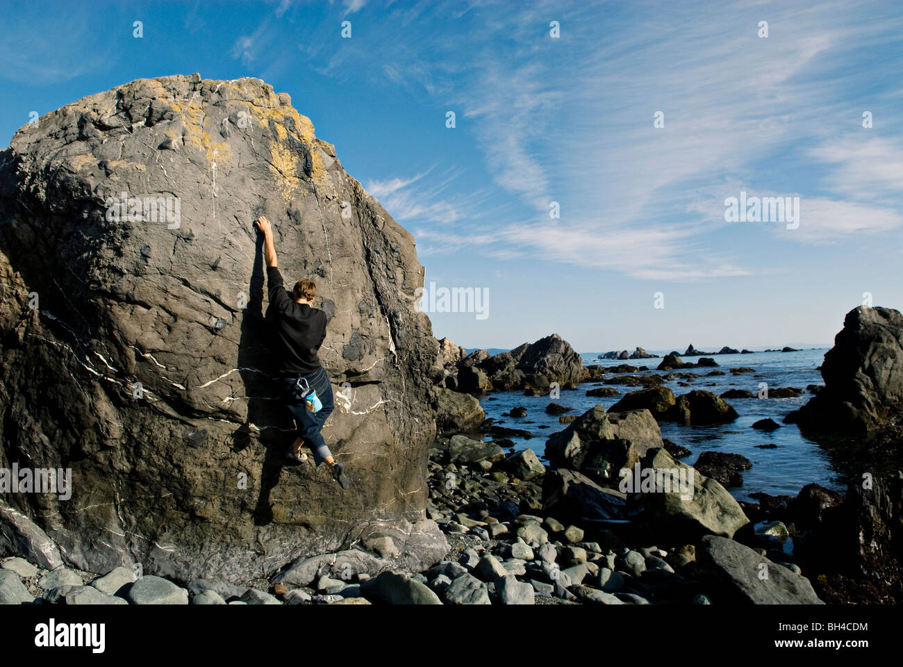 A young man reaches for a hold, while bouldering near the ocean in Cresent City, California. - Stock Image