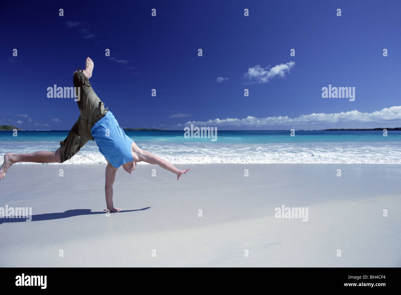 Young man performing a cart wheel on a deserted tropical beach - Stock Image