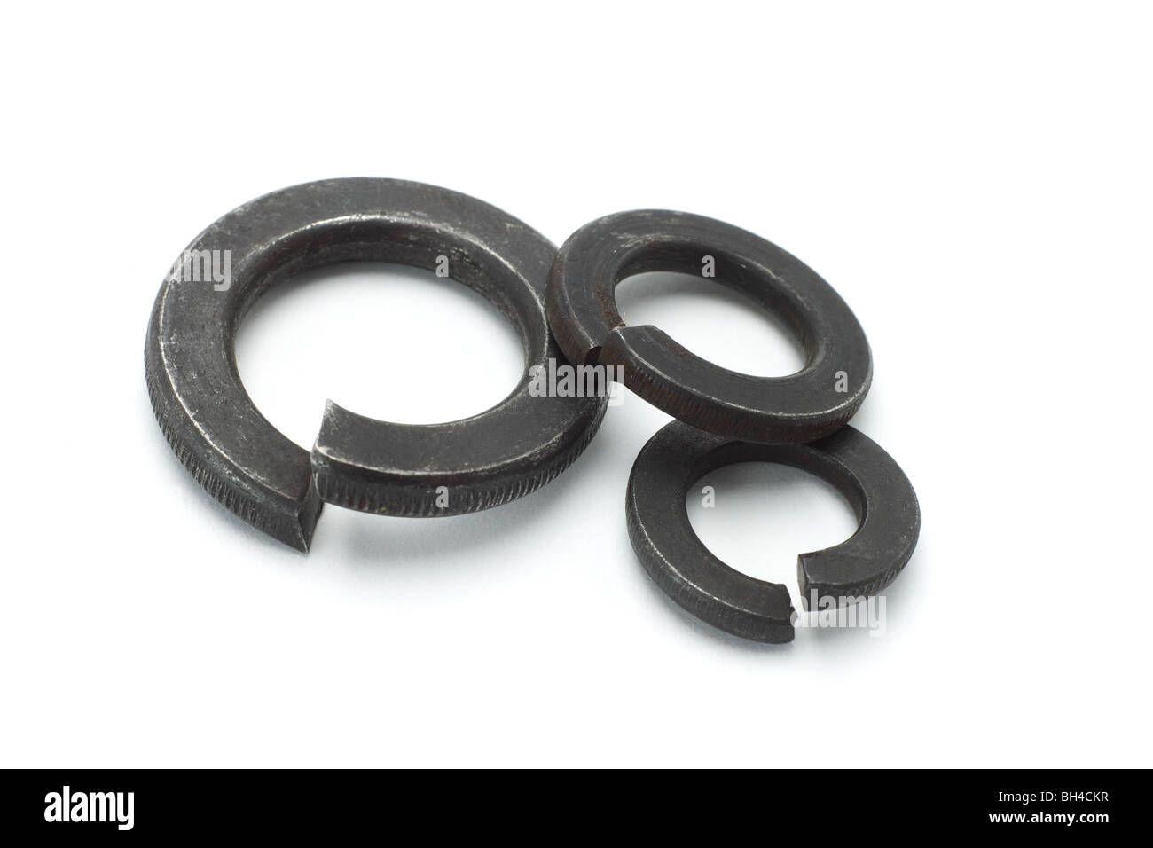 Three used metal washers on white background - Stock Image