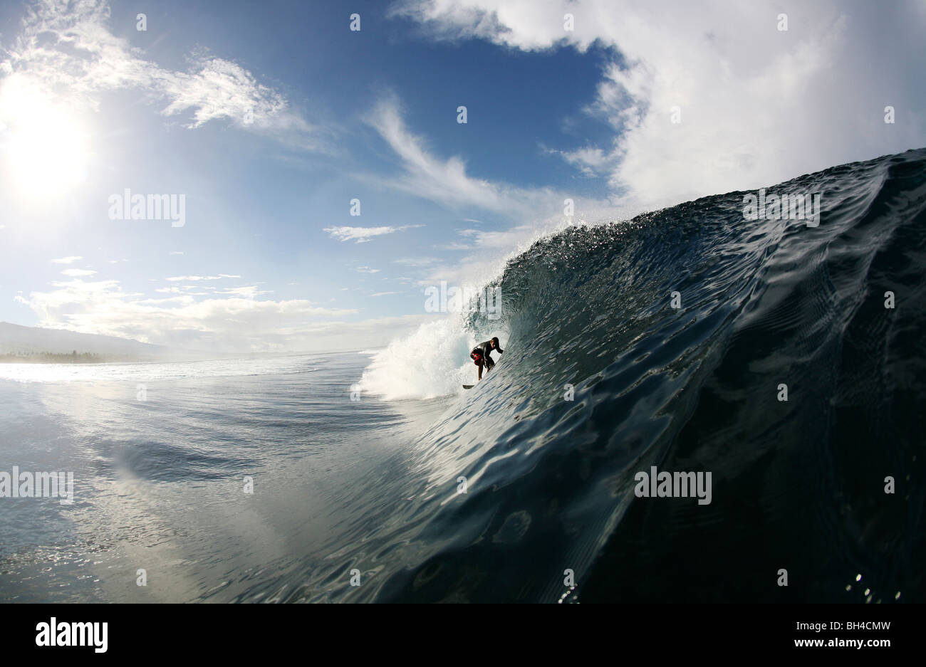 A surfer enters a barrel wave at Maninoa, Upolu, Samoa. - Stock Image