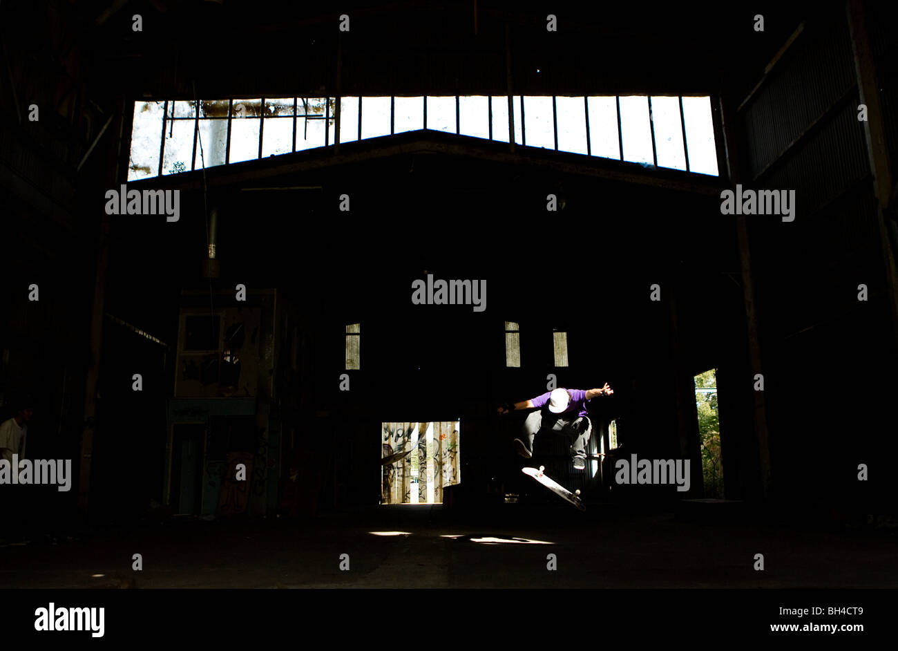 A skater performs a kick flip in an abandoned warehouse on the Central Coast, New South Wales, Australia. - Stock Image