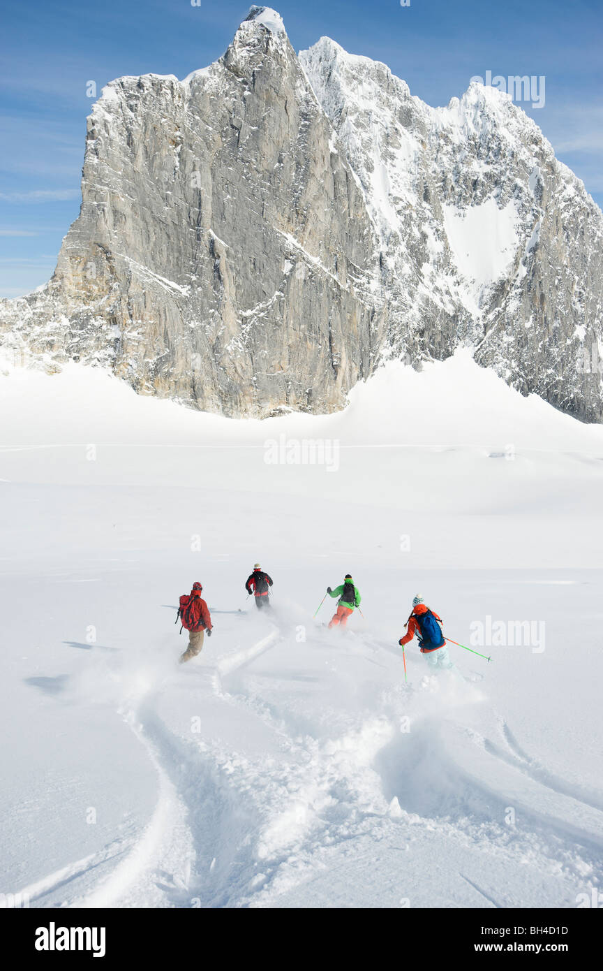 A group of backcountry skiers cross tracks in the Selkirk Mountains, Canada. - Stock Image