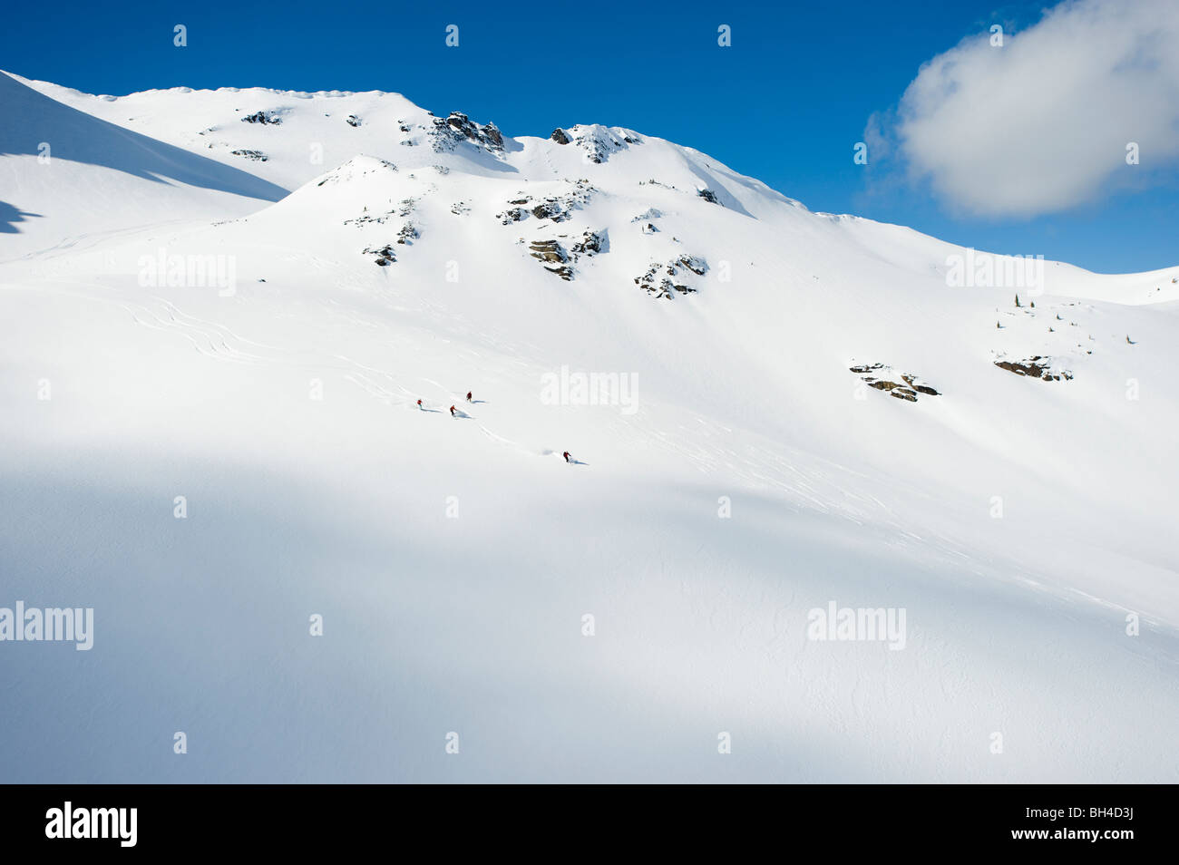 A group of skiers take a run down a large alpine bowl in the backcountry of the Selkirk Mountains, Canada. - Stock Image