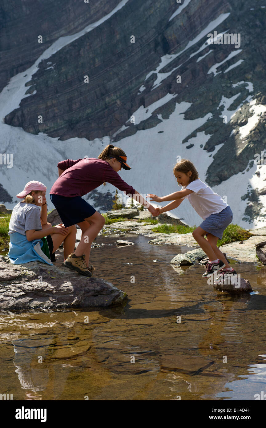 A young girl helps her sister cross a pool of water and onto a rock in Glacier National Park, Montana. - Stock Image