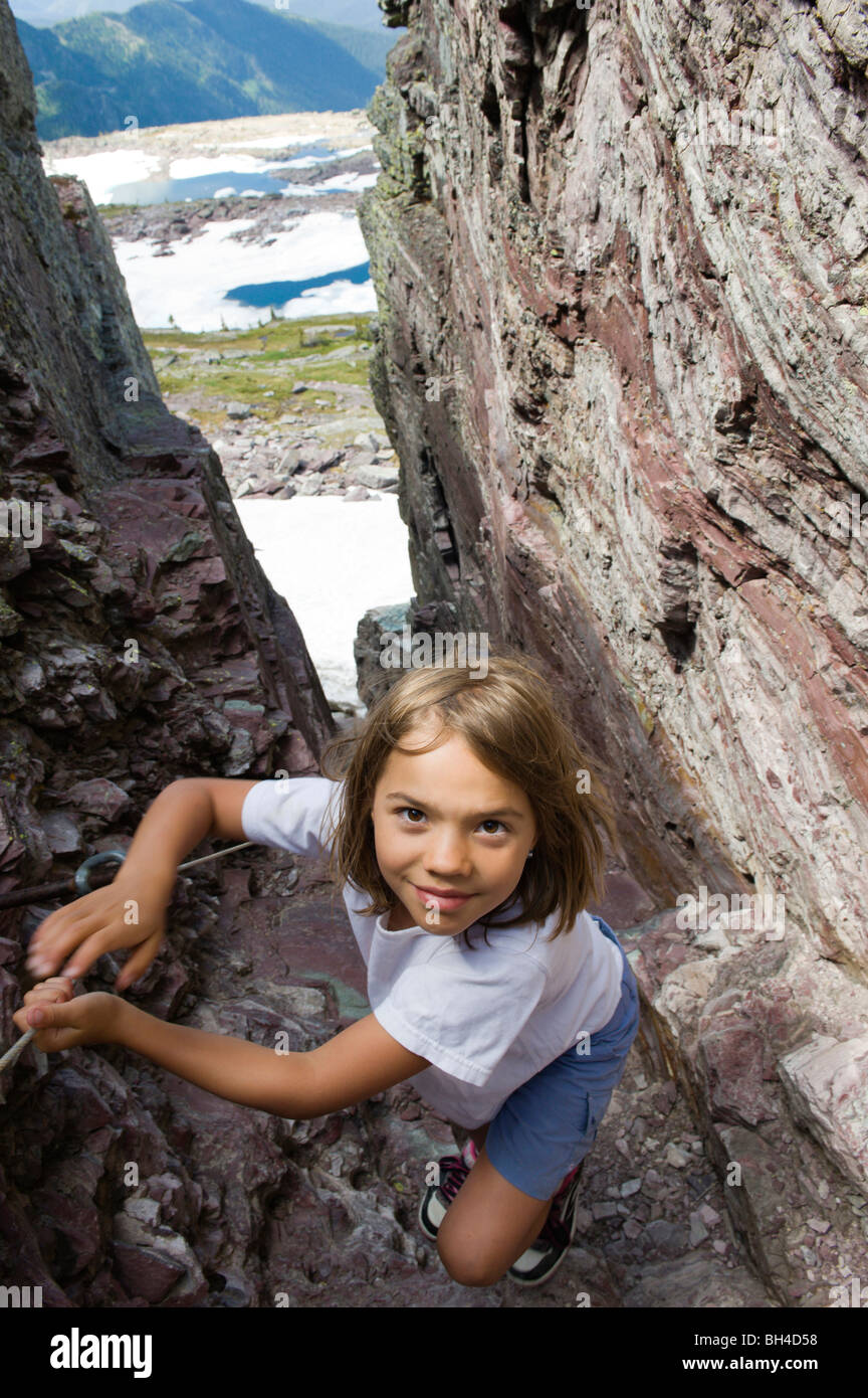 A young girl makes her way up a narrow slot in a cliff while hiking in Glacier National Park, Montana. Stock Photo