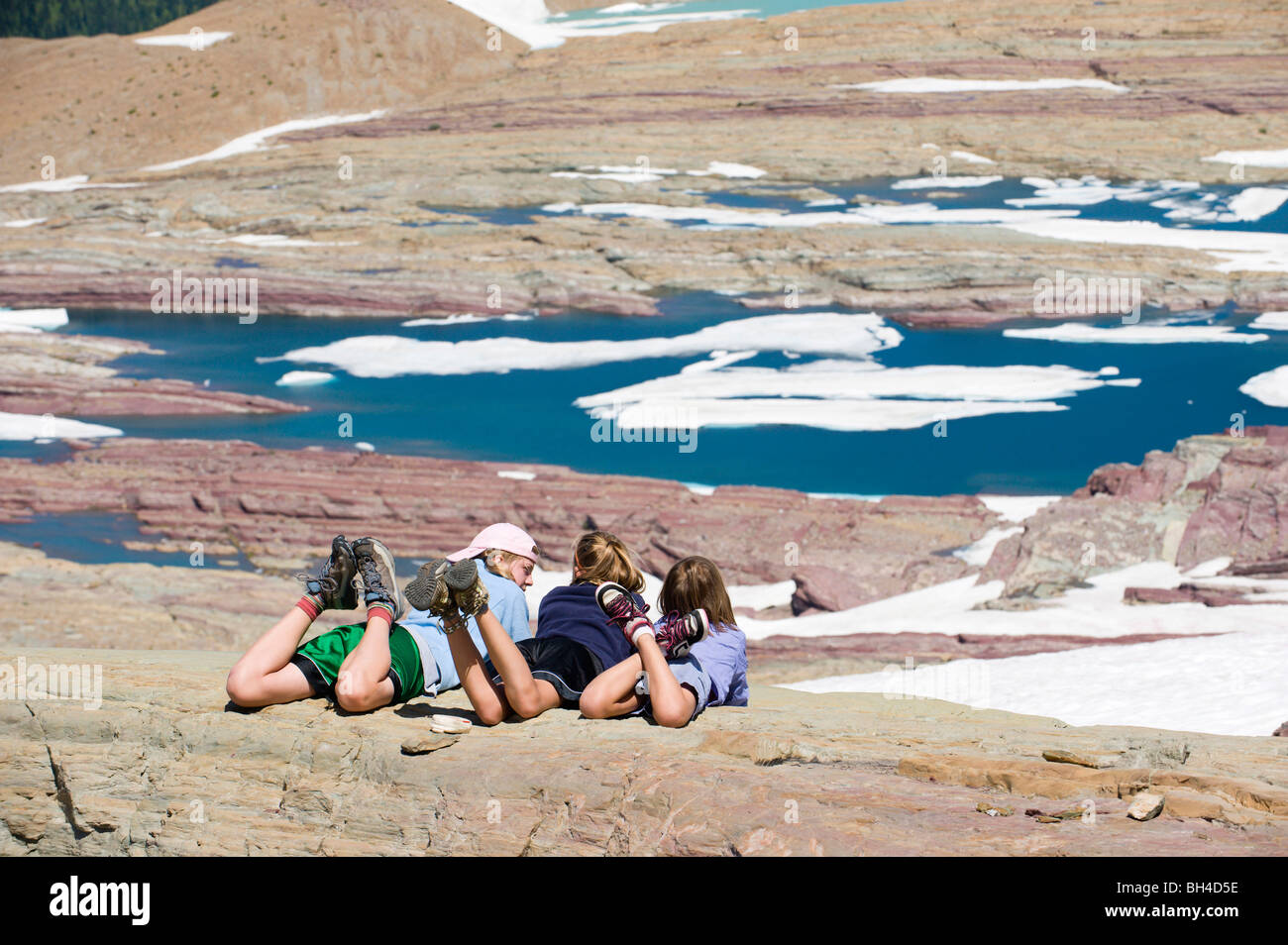 Three young girls relax and soak up the sunshine overlooking a glacier lake in Glacier National Park, Montana. - Stock Image