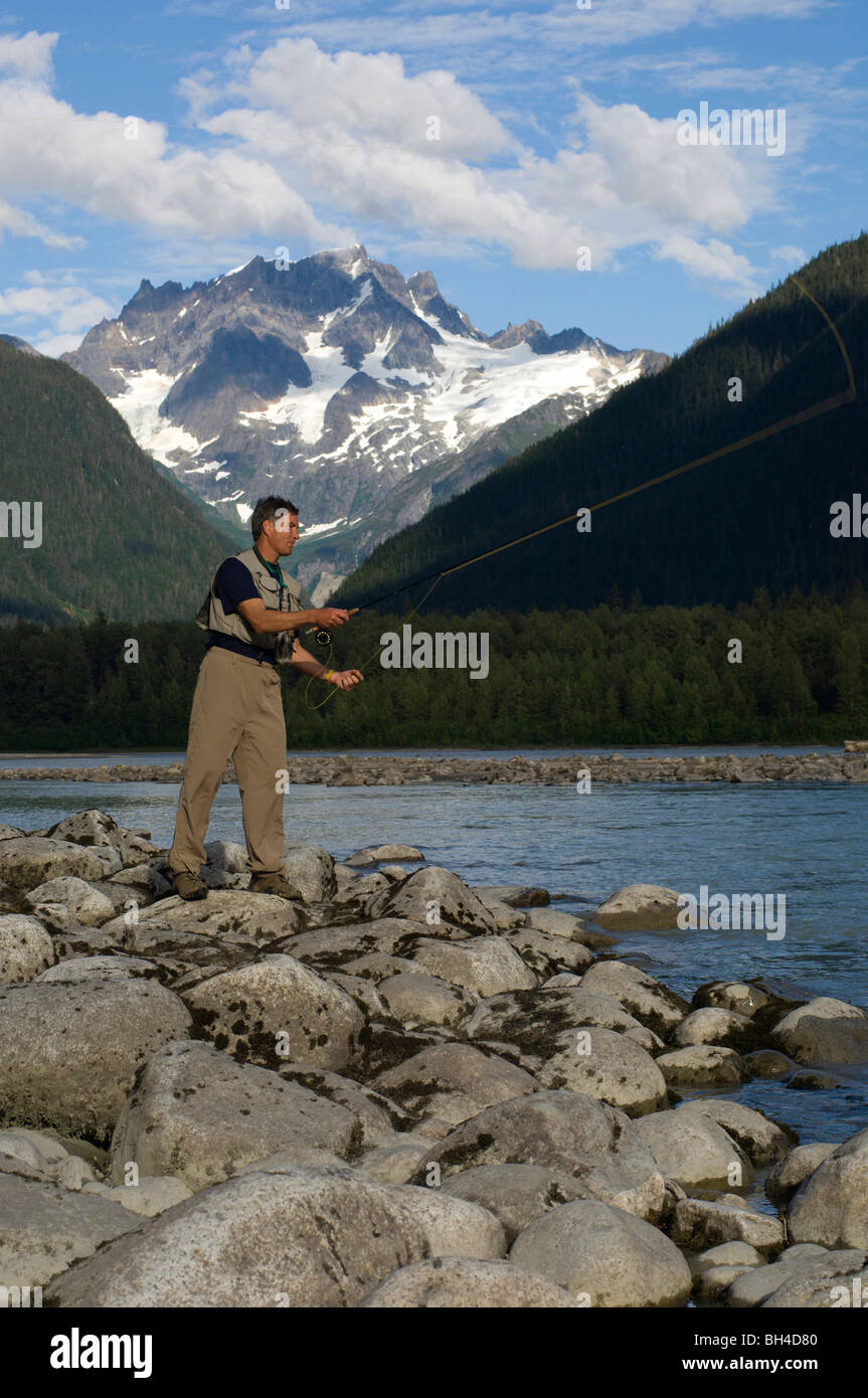 A man fly fishes a stream in British Columbia, Canada. - Stock Image