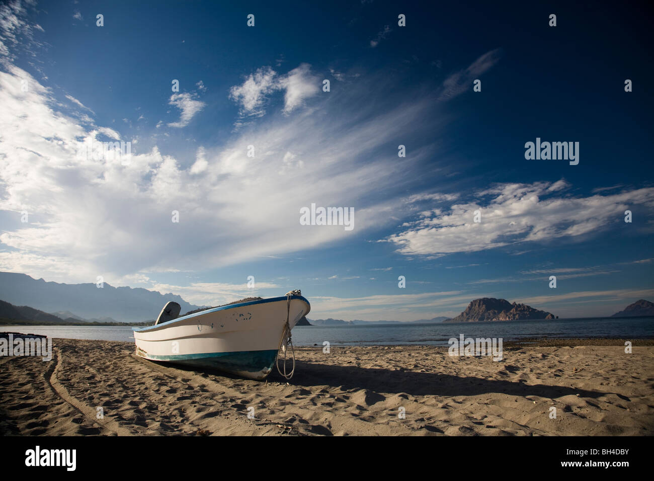 A boat sits on the sand on an empty beach beneath a partly cloudy sky in Loreto, Baja California Sur, Mexico. - Stock Image