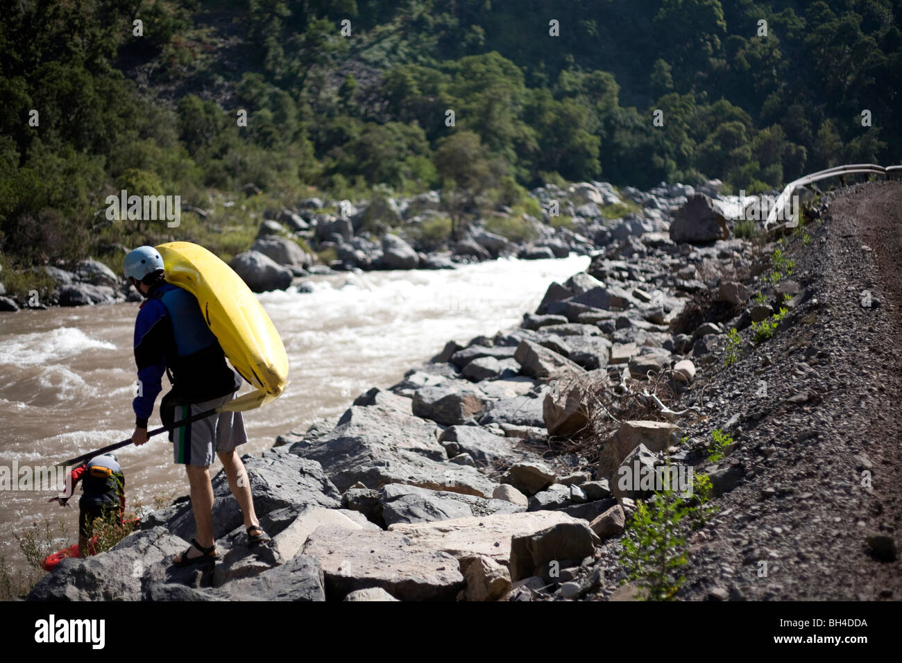 A female kayaker carries a kayak to the put-in on a river. - Stock Image