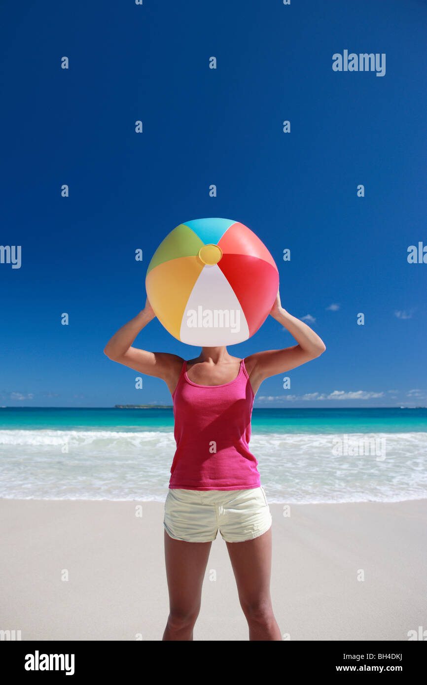 Young woman holding an inflatable beach ball over her face on a deserted tropical beach - Stock Image