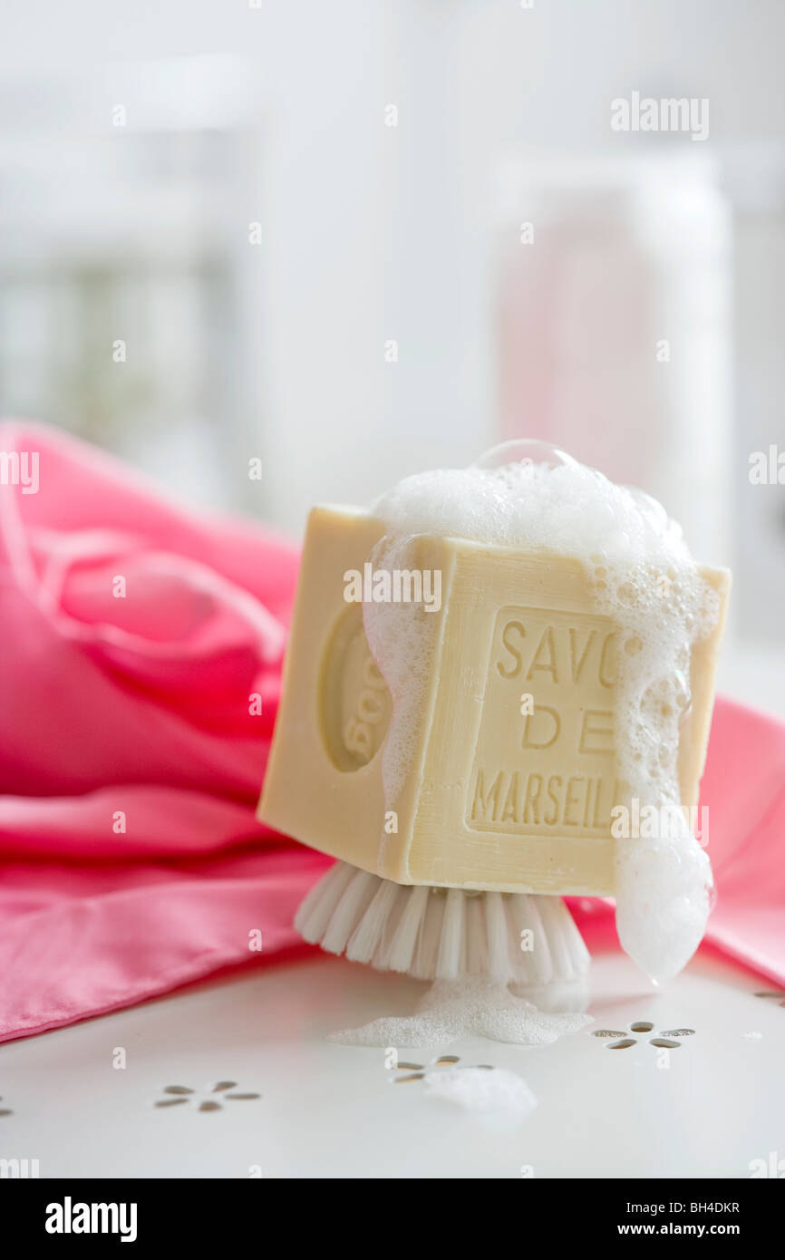 Shave brush with soap suds on a bathroom counter - Stock Image
