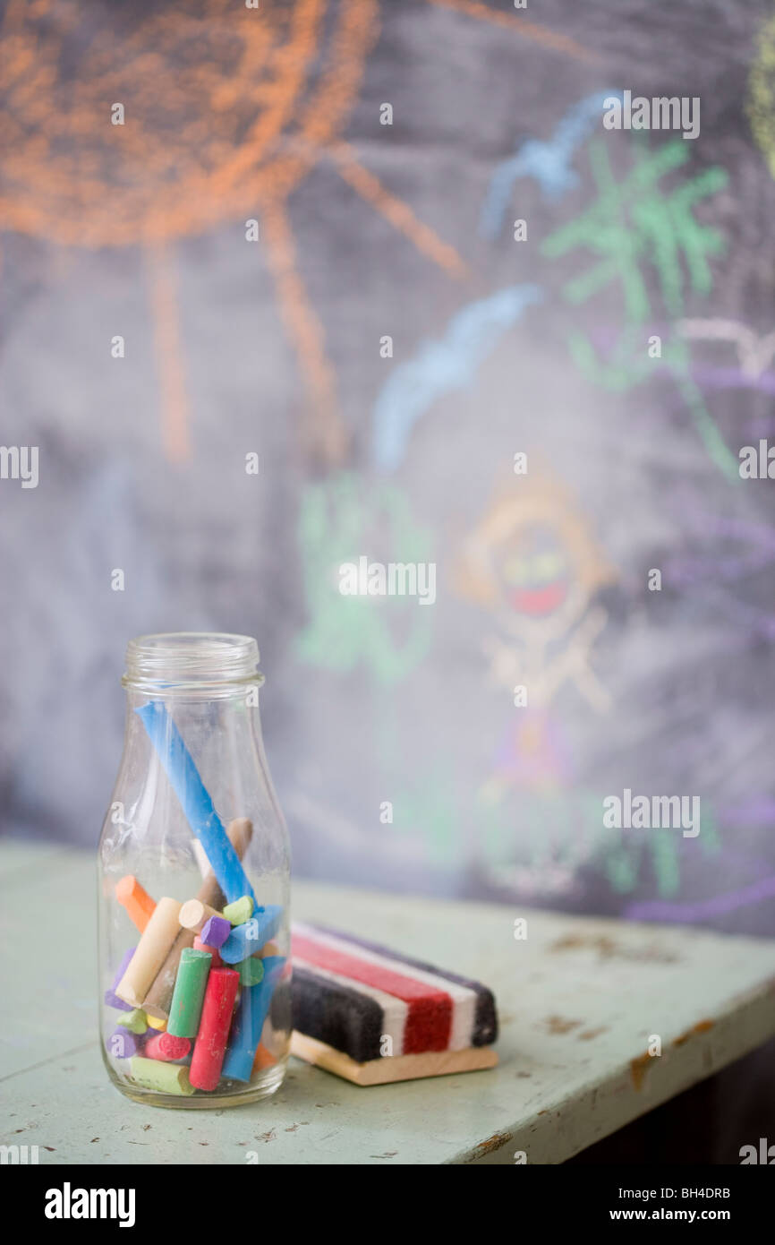 Chalk and an eraser in front of a chalk board - Stock Image