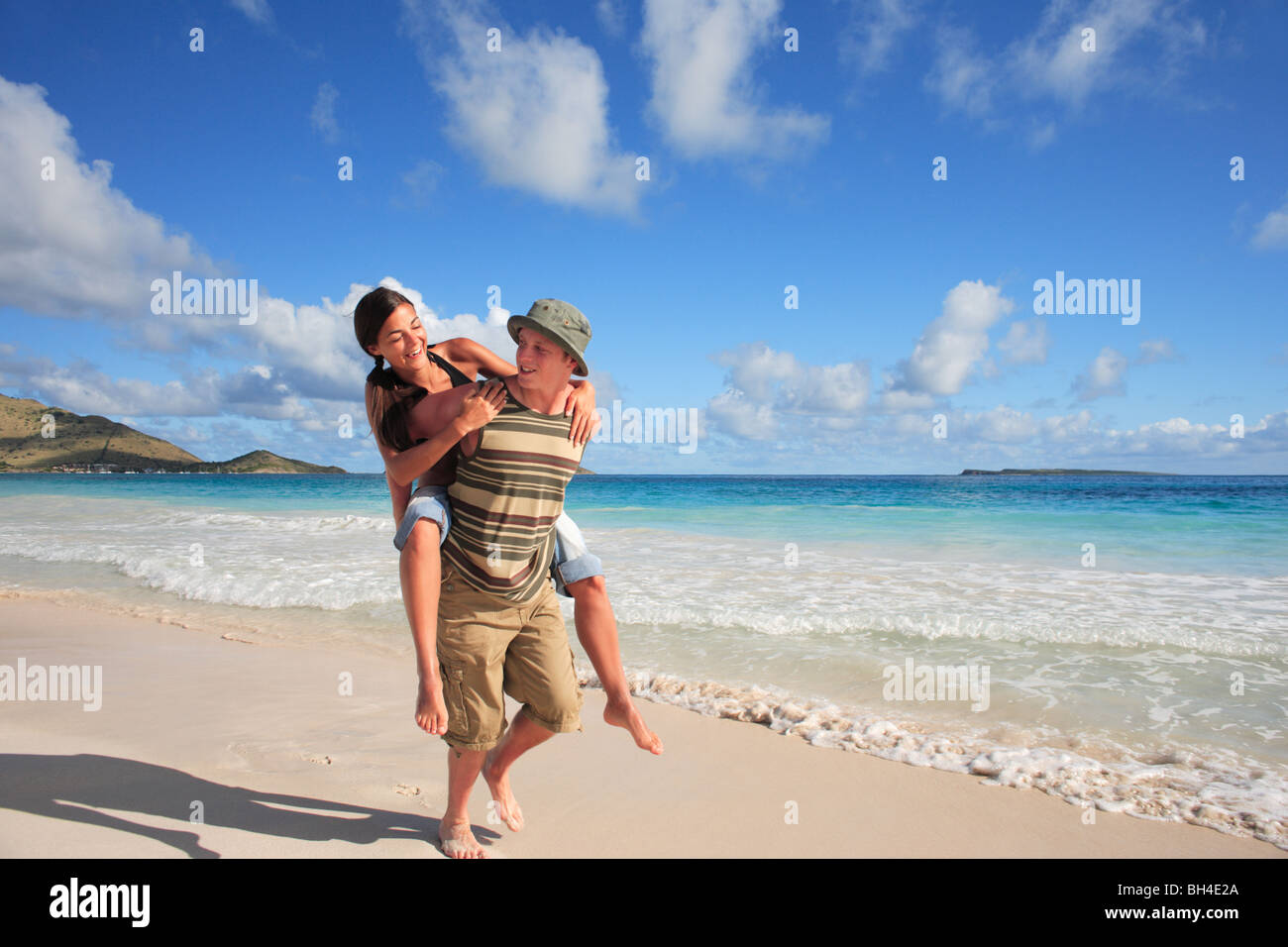 Young couple playing piggyback on a deserted tropical beach, laughing - Stock Image