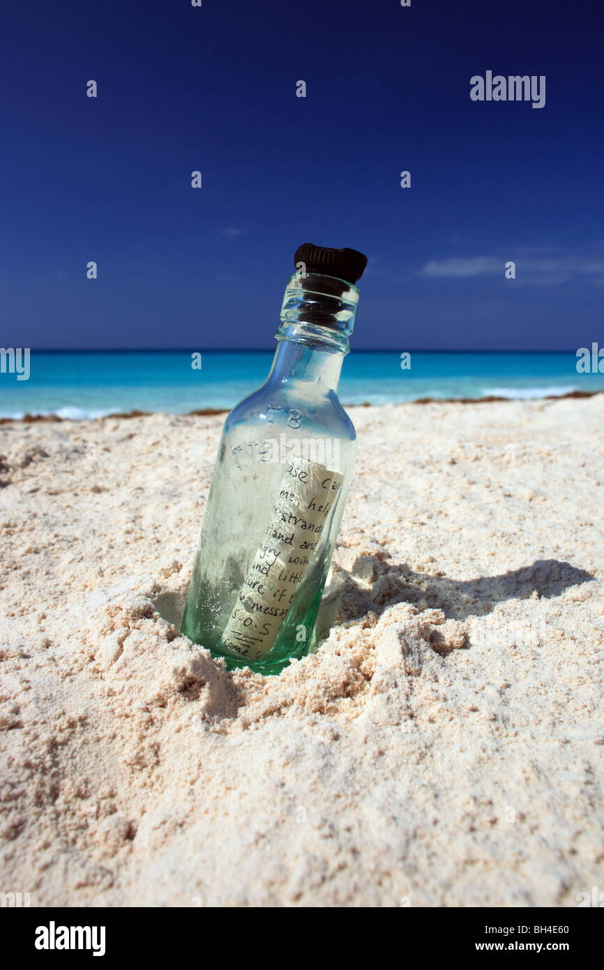 A message in a bottle in the sand on a deserted tropical beach - Stock Image