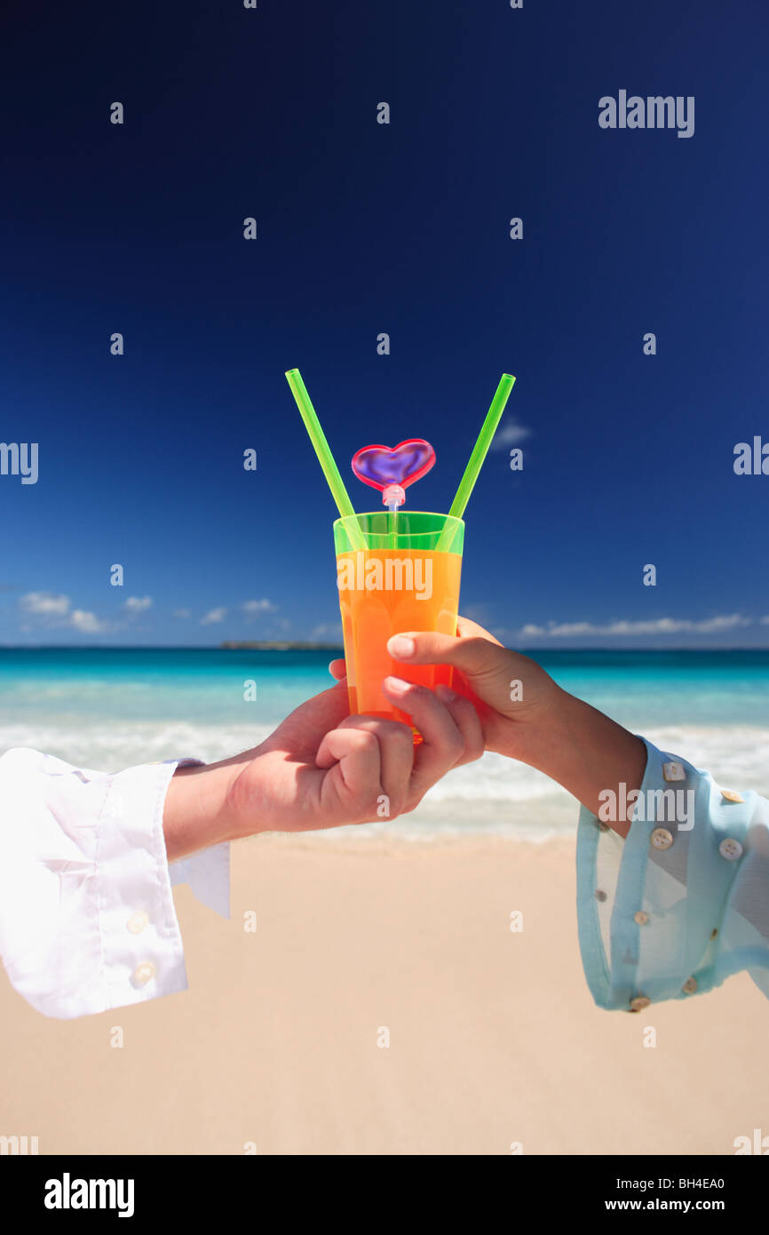 Young couple holding a single tropical cocktail on a deserted tropical beach - Stock Image