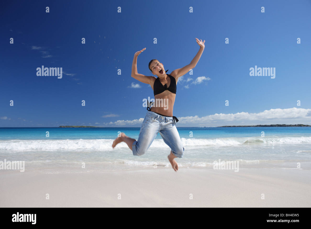 Young woman leaping in the air on a deserted tropical beach, smiling - Stock Image