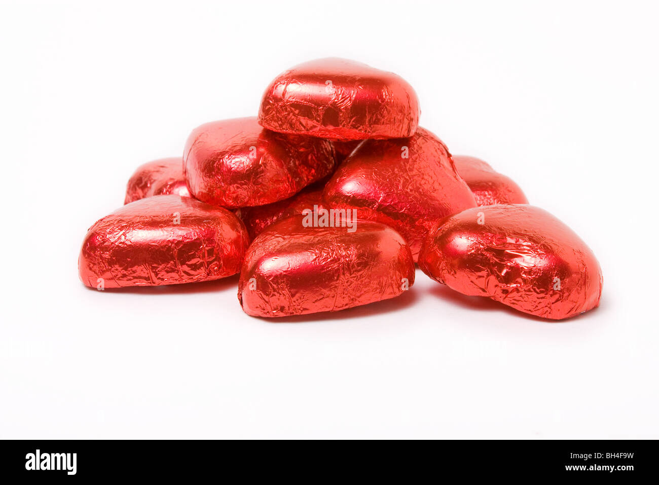 Red foil wrapped chocolate hearts for valentine's day - Stock Image