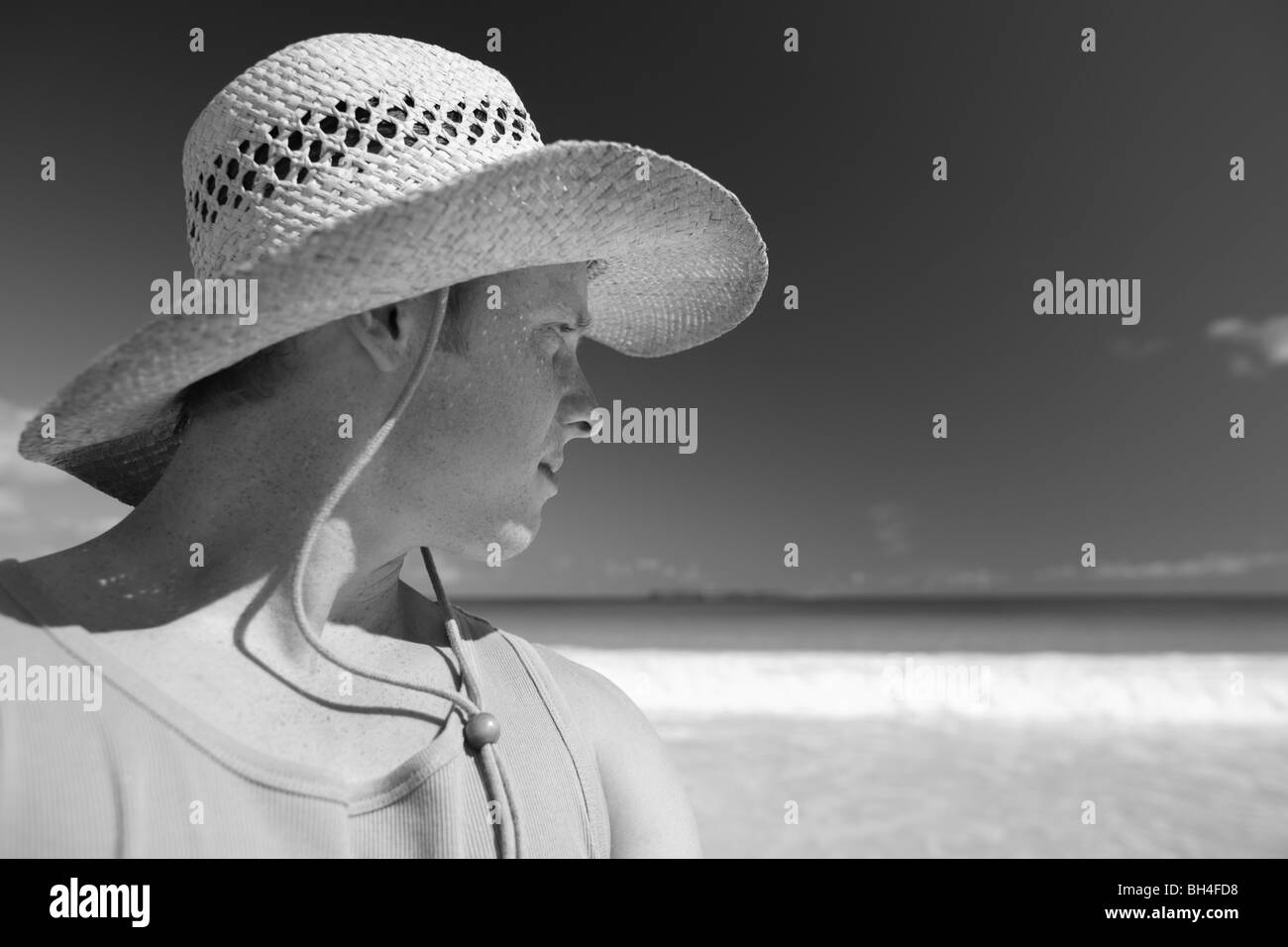 Young man wearing a straw hat looking towards the sea on a tropical beach - Stock Image