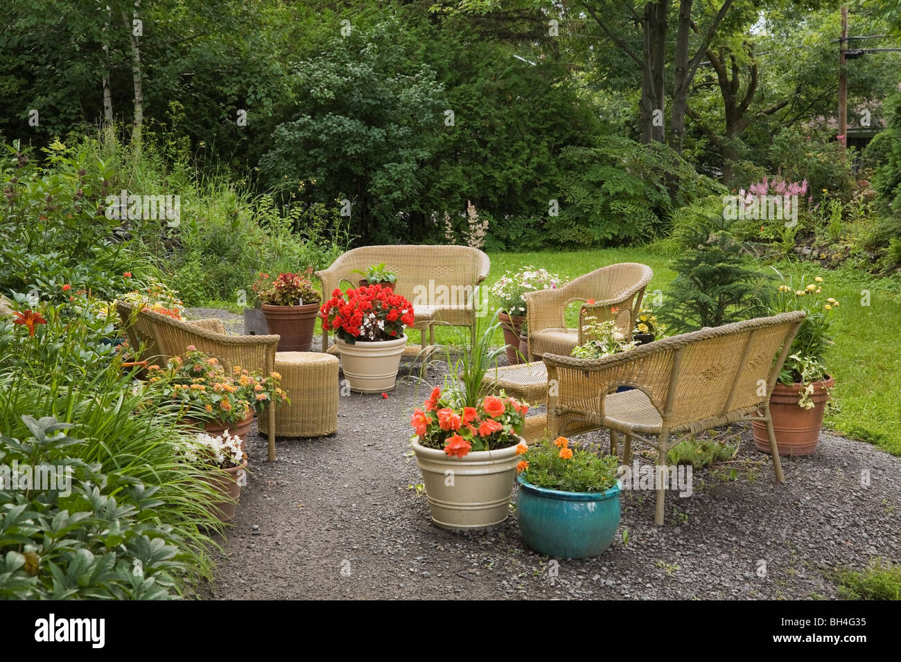 Potted plants and wicker furniture in front yard, Laval, Quebec - Stock Image