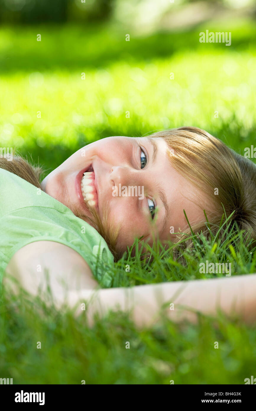Portrait of young girl laying in grass - Stock Image