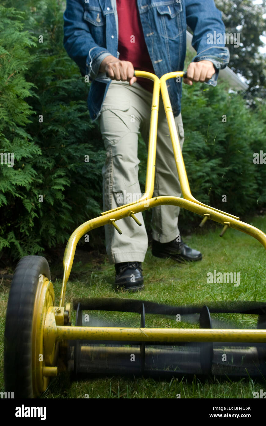 Man mowing lawn with eco-friendly push mower, Montreal, Quebec - Stock Image
