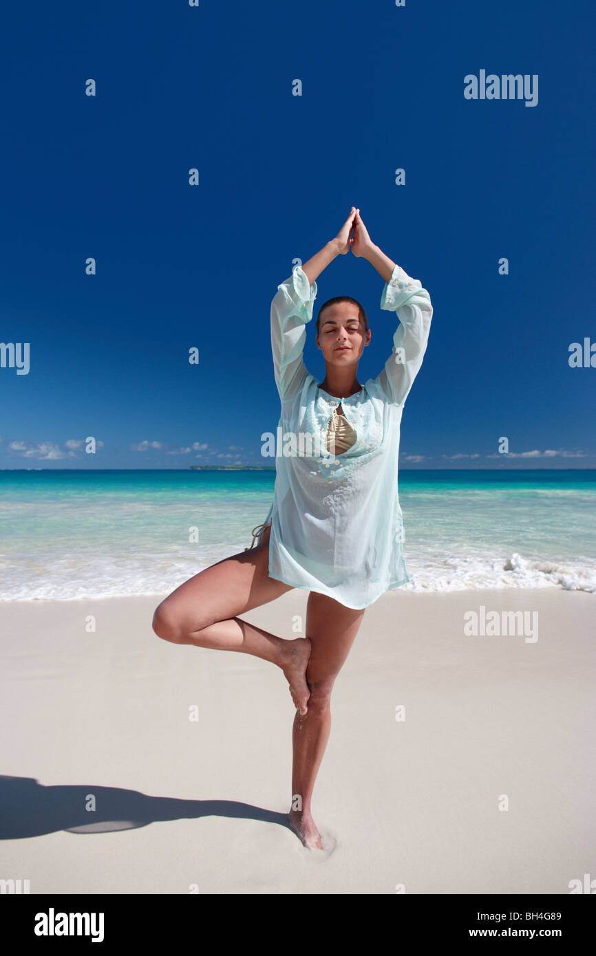 A young woman practicing Tai Chi on a deserted tropical beach - Stock Image