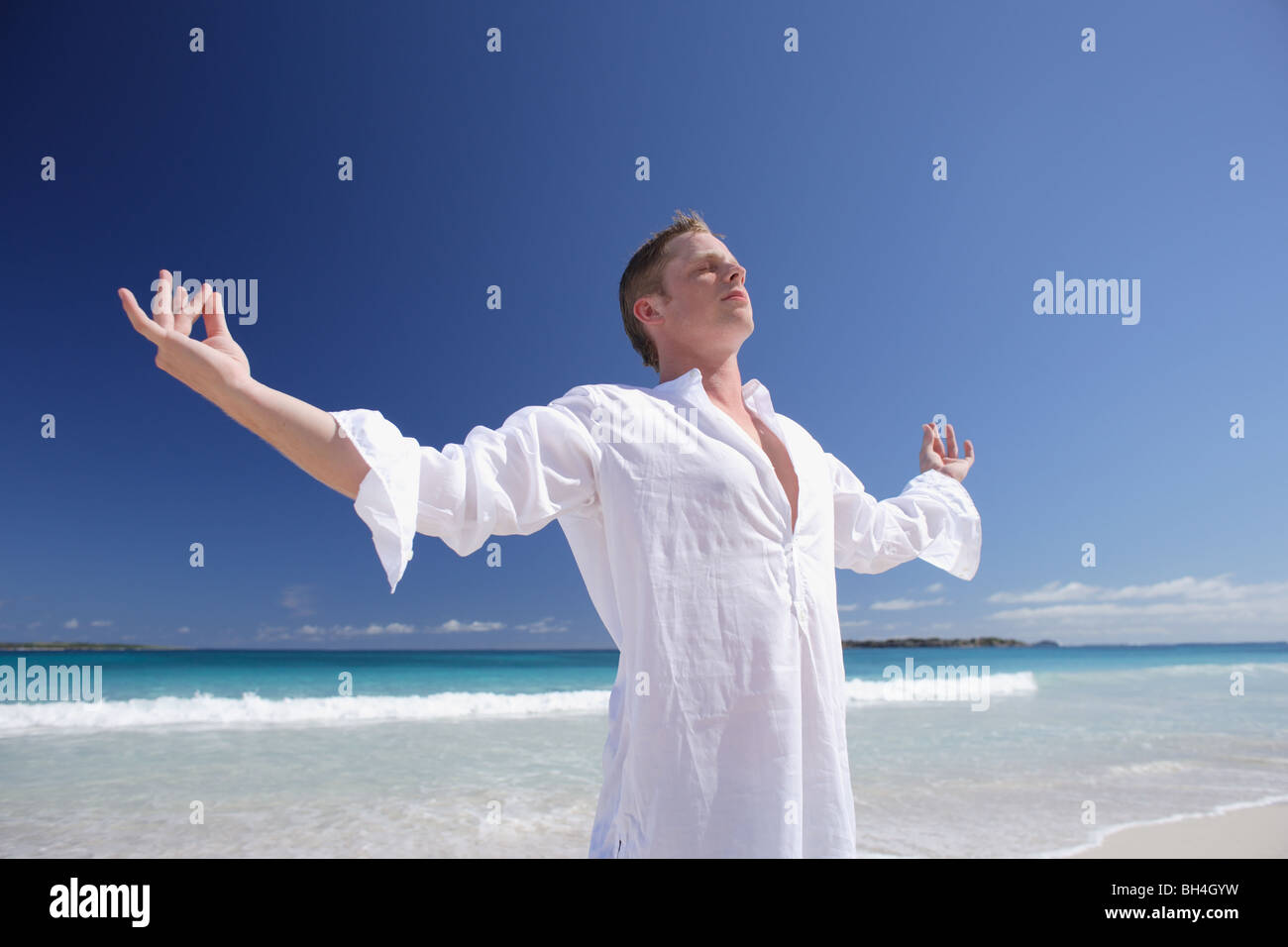 A young man practicing Tai Chi on a deserted tropical beach - Stock Image