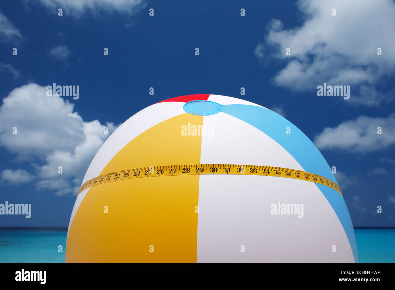 A tape measure wrapped around a brightly colored inflatable beach ball against a tropical blue sea and sky - Stock Image