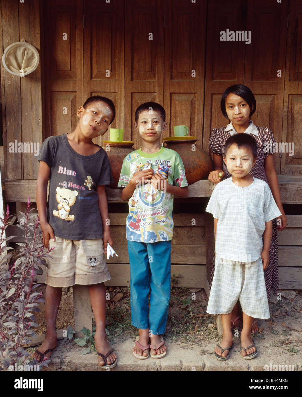 4 four children posing in front of a house and clay jugs with water Vier Kinder posieren vor Trinkwasserkrügen - Stock Image