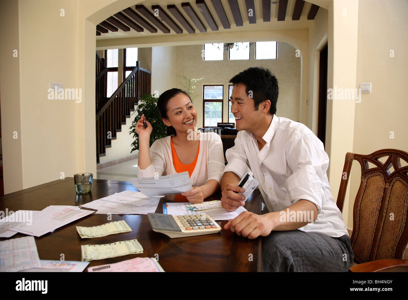 Chinese young couple sitting at table with bank statements - Stock Image