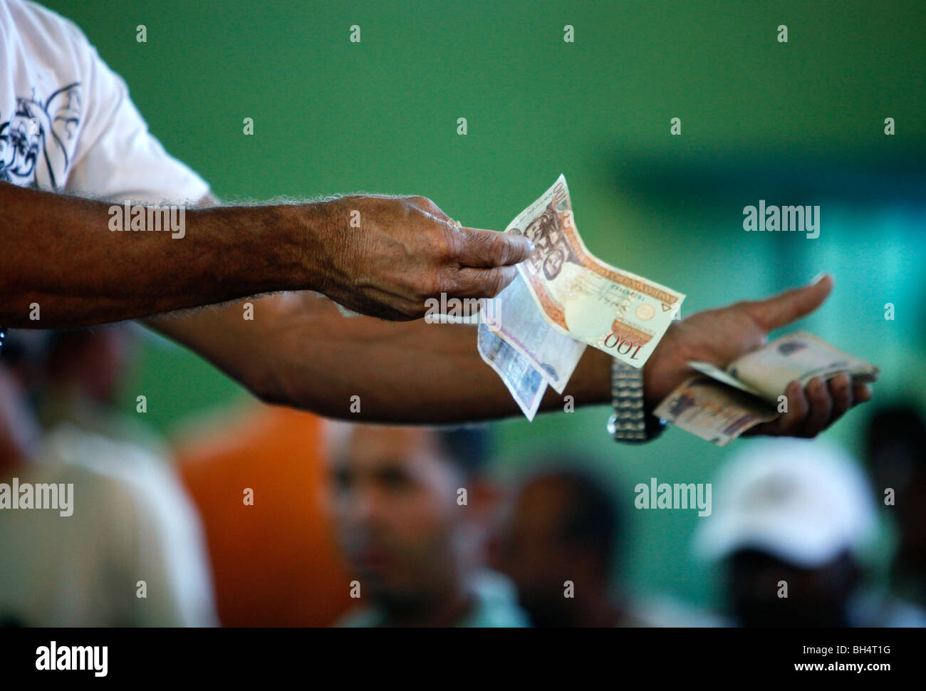 Betting money changes hands at a cockfight, Dominican Republic Stock Photo