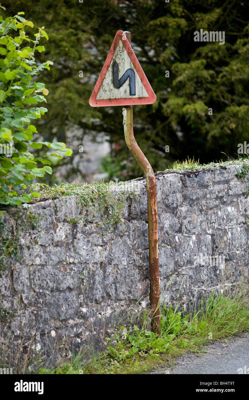 Double bend first to the left road sign. Crooked sign on crooked post. Pen-y-Dyffryn. Wales. United Kingdom. - Stock Image