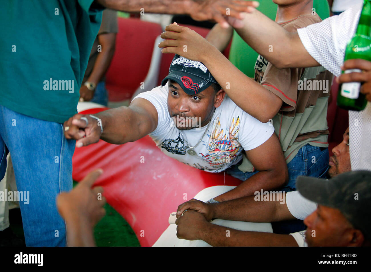 Men bet amongst each other with signals and gestures at a cockfighting ring, Dominican Republic Stock Photo