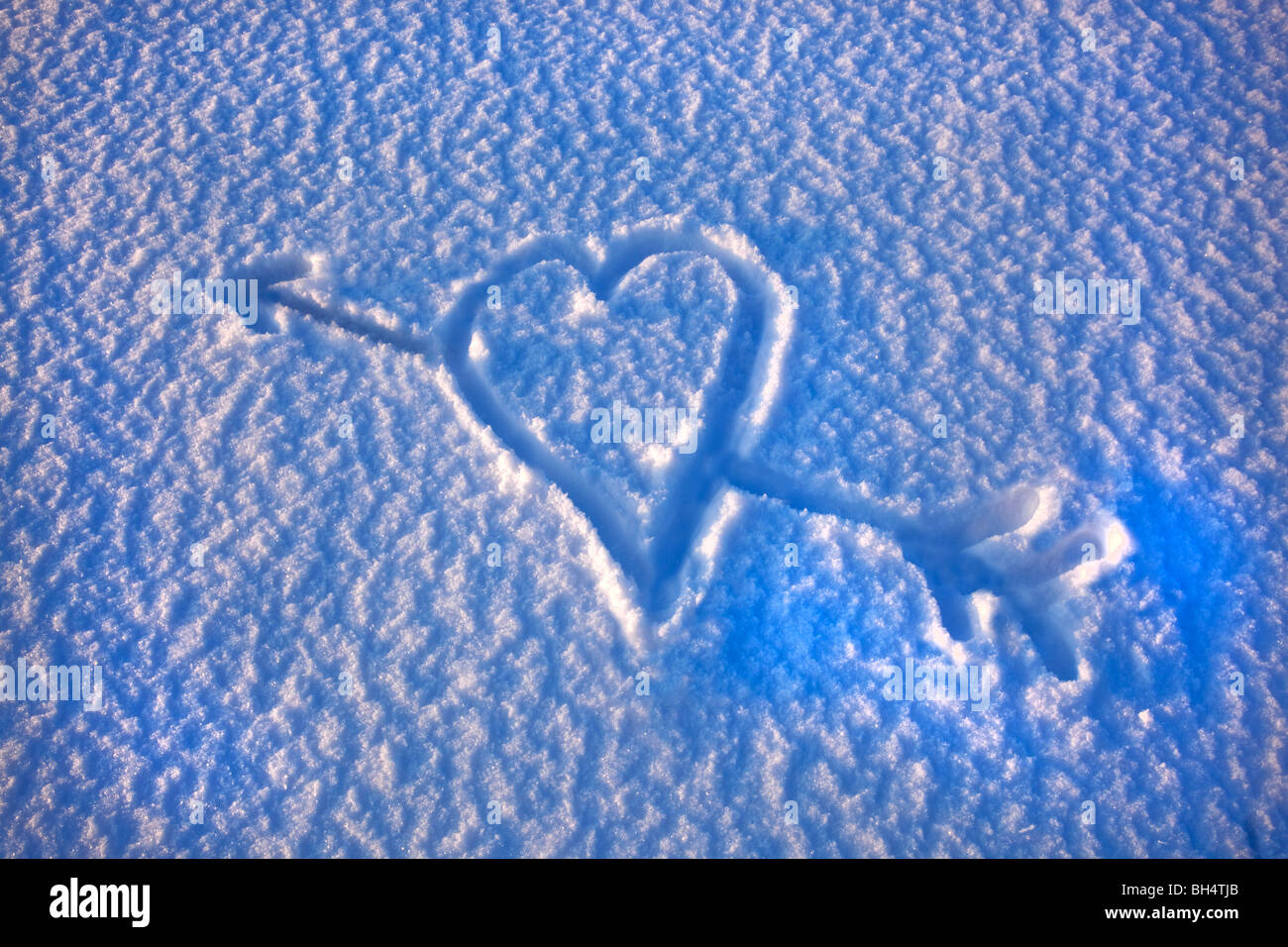 a love heart with cupids arrow through it drawn in the snow - Stock Image