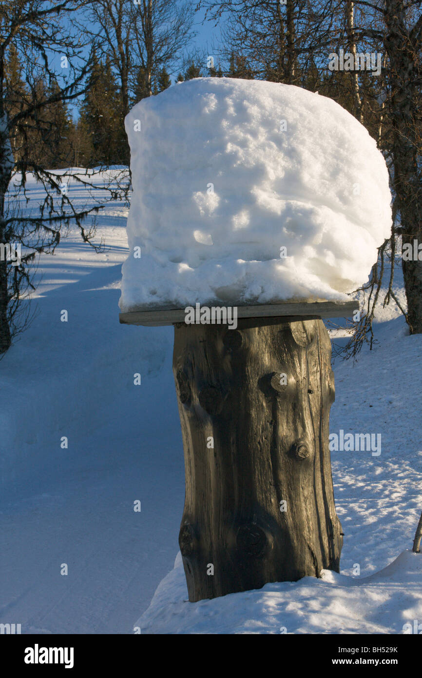 Rustic gatepost in snow with stack of snow on top. - Stock Image