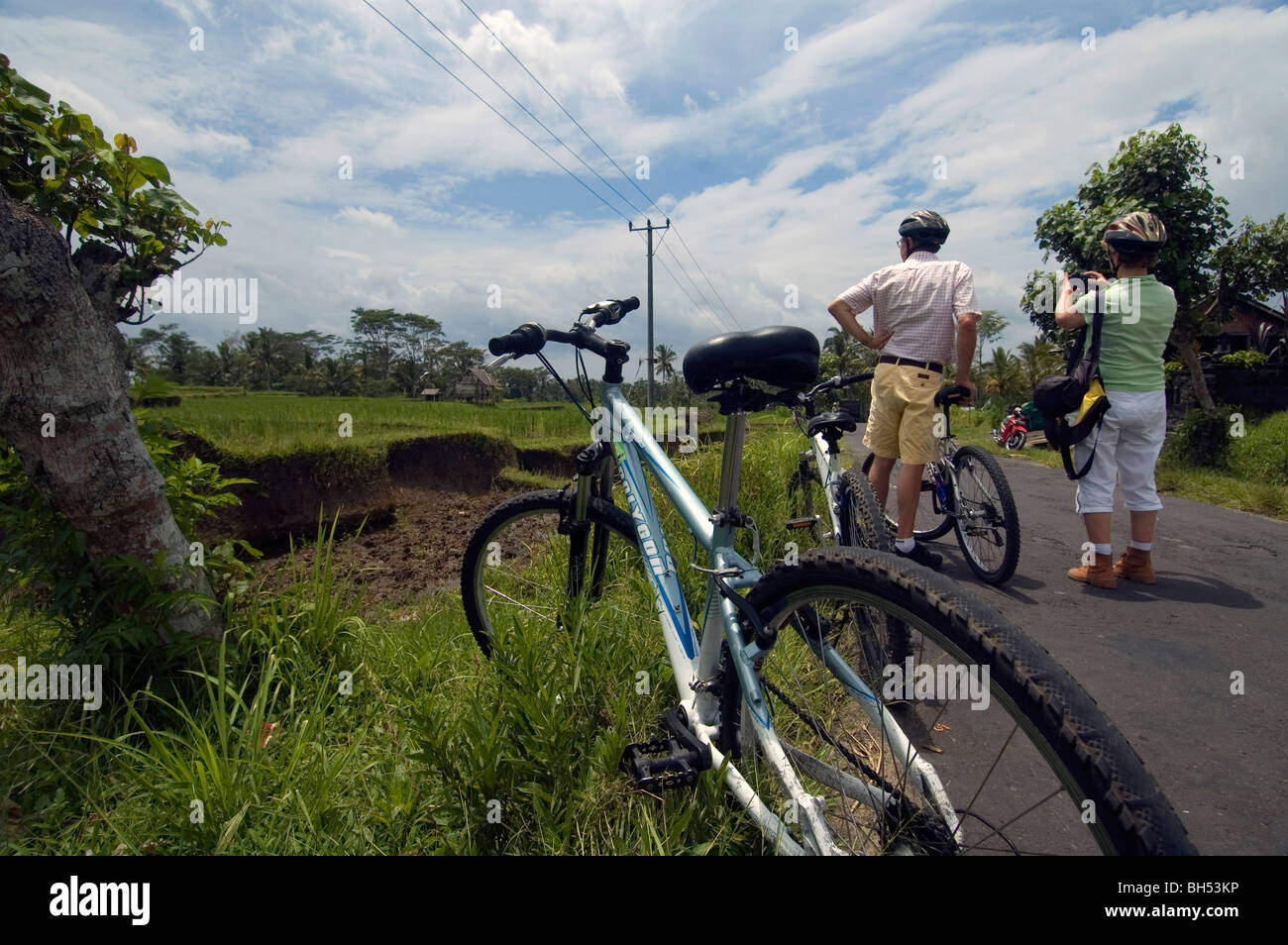 Middle-aged tourist couple pause for a photo on a bicycle tour in Bali, Indonesia. No MR or PR Stock Photo