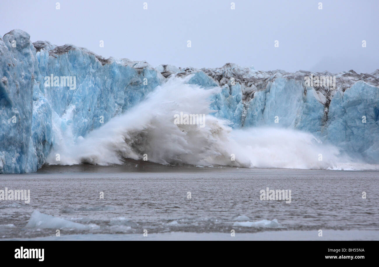 Glacier of blue ice calving into the ocean creating a huge splash and following wave - Stock Image
